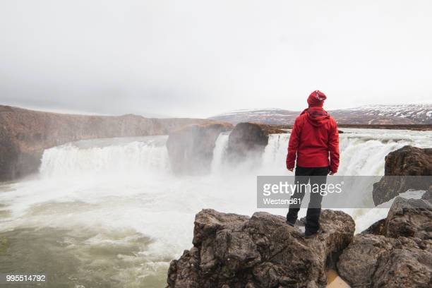 iceland, man standing at godafoss waterfall - red coat stock pictures, royalty-free photos & images