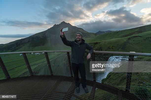 Iceland, Man taking selfie at Skogafoss waterfall