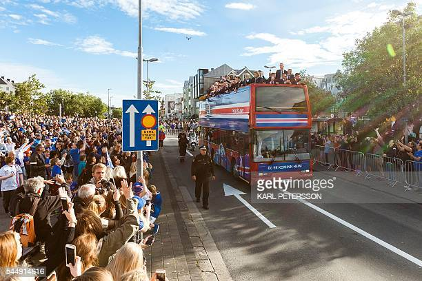 Iceland national football team arrives in Reykjavik on July 4 2016 on a bus while people in the streets greet them as winners after they lost against...