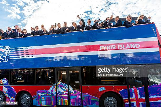 TOPSHOT Iceland national football team arrives in Reykjavik on July 4 2016 on a bus while people in the streets greet them as winners after they lost...