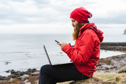 Iceland, North of Iceland, man with laptop sitting near the sea using cell phone - gettyimageskorea