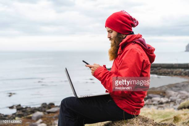 Iceland, North of Iceland, man with laptop sitting near the sea using cell phone