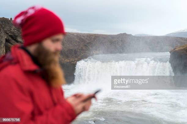 Iceland, North of Iceland, young man using smartphone, waterfall in the background