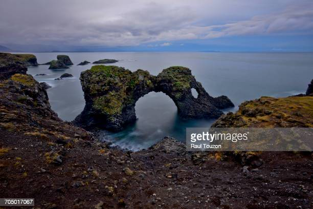 A natural arch in sea off the coast of Iceland.