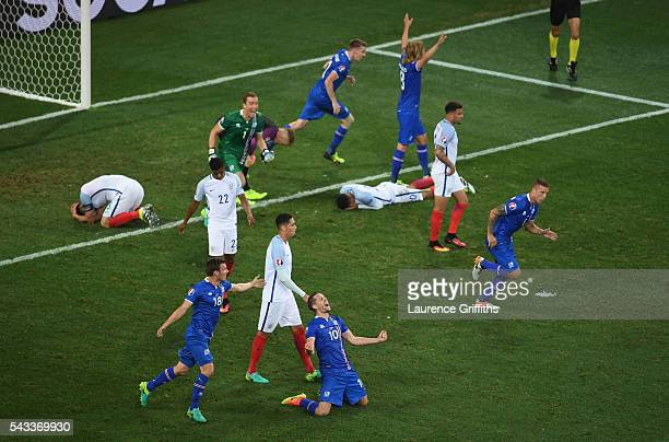 Iceland players celebrate while England players show dejection after the UEFA EURO 2016 round of 16 match between England and Iceland at Allianz...