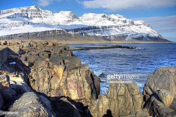 Iceland, snowy mountain with gigantic rocks in foreground