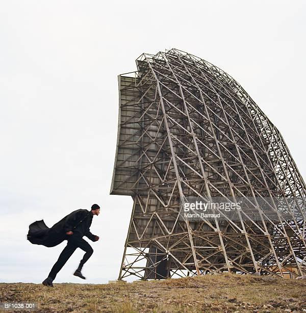 Iceland, Stokksnes, man running behind radar dish, coat billowing