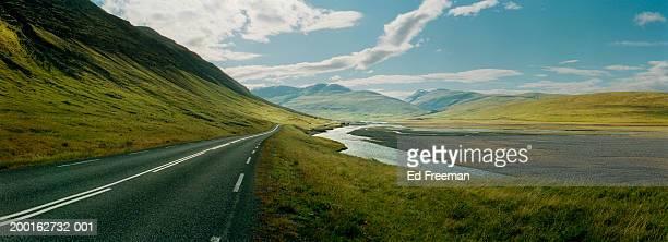 iceland, two lane road by stream (digital enhancement) - アイスランド ストックフォトと画像