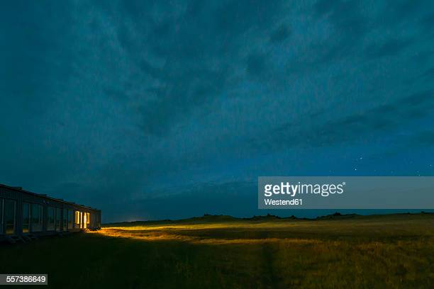 iceland, view to lighted motel by night - motel stock photos and pictures