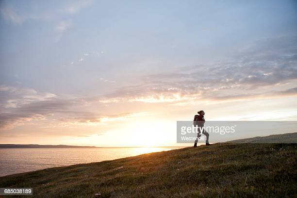 Iceland, woman hiking upon a hill at twilight