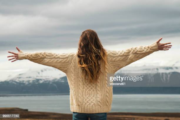 iceland, woman standing at lakeside with outstretched arms - arms outstretched stock pictures, royalty-free photos & images