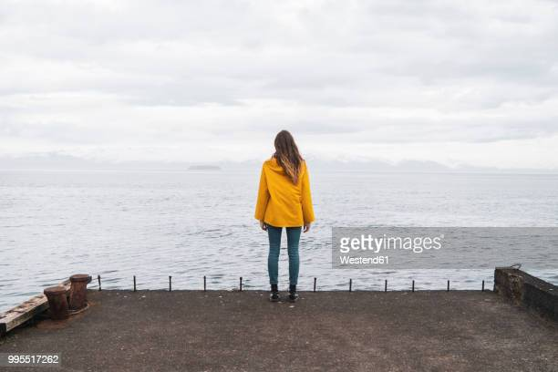 Iceland, woman standing at the sea