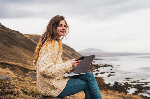 Iceland, woman using laptop and cell phone at the coast - gettyimageskorea