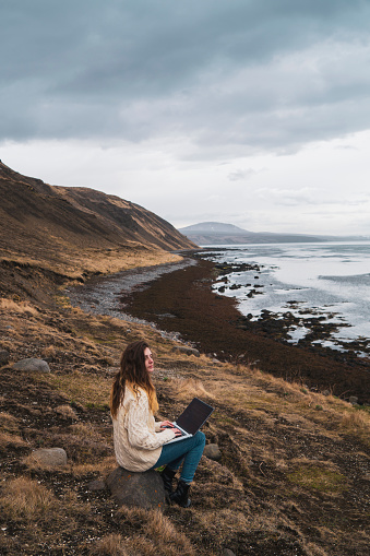 Iceland, woman using laptop at the coast - gettyimageskorea