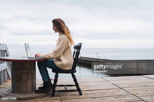iceland, woman using laptop at the sea - ウォーターフロント ストックフォトと画像