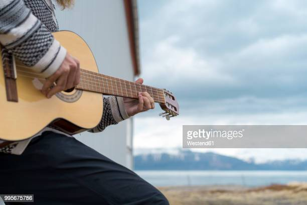Iceland, young man playing guitar
