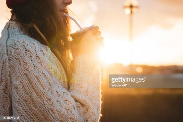 Iceland, young woman with coffee to go at sunset