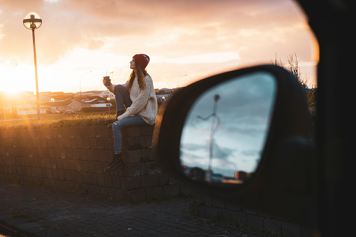 Iceland, young woman with coffee to go at sunset, wing mirror - gettyimageskorea