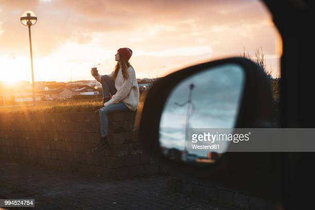 iceland, young woman with coffee to go at sunset, wing mirror - moody sky stock pictures, royalty-free photos & images