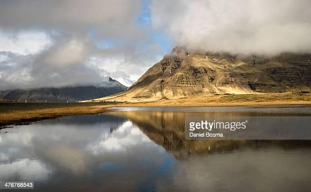 icelandic clouds and mountains reflected - austurland stock-fotos und bilder