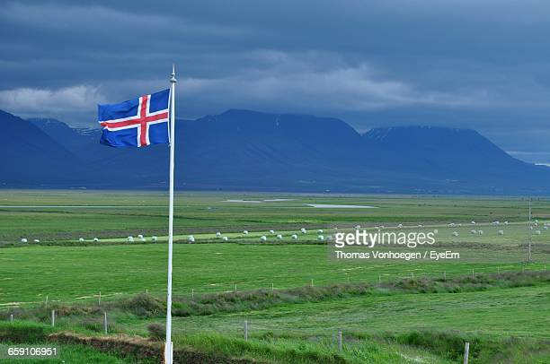 Icelandic Flag Against Scenic Green Landscape And Mountains Against Cloudy Sky