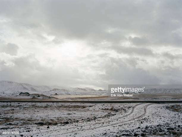 icelandic landscape of snow covered road - overcast stock pictures, royalty-free photos & images