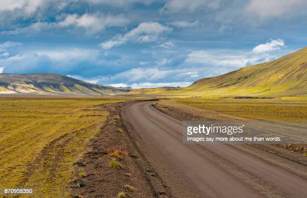 Icelandic road with hills and heavy sky. Landscape.