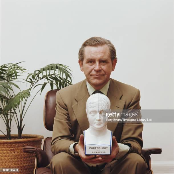 Icelandic television presenter Magnus Magnusson of 'Mastermind' with an L N Fowler phrenology head circa 1977