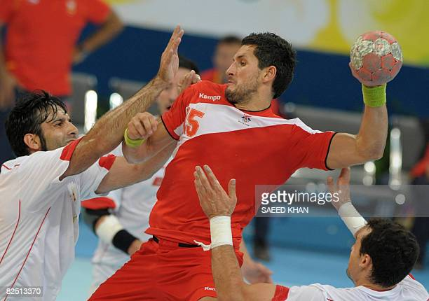 Iceland's Alexander Petersson is marked as he aims at the goal of Spain during a men's handball semifinal of the 2008 Beijing Olympic Games against...