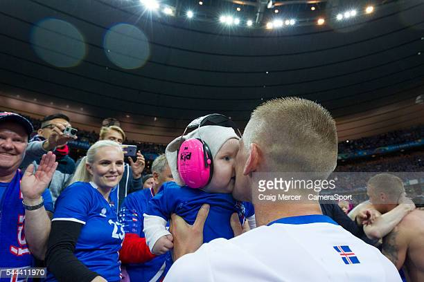 Iceland's Ari Freyr Skulason kisses his baby child at the end of the match during the UEFA Euro 2016 Quarterfinal match between France and Iceland at...