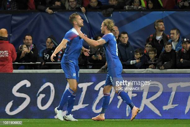 Iceland's defender Kari Arnason celebrates with Iceland's midfielder Birkir Bjarnason during the friendly football match between France and Iceland...