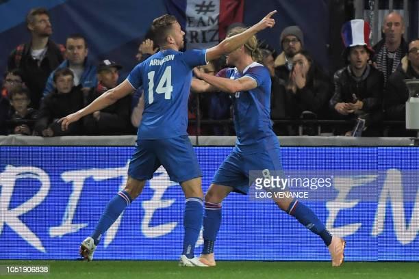 Iceland's defender Kari Arnason celebrates with Iceland's midfielder Birkir Bjarnason during the friendly football match between France and Iceland...