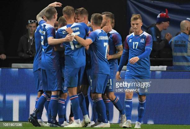Iceland's defender Kari Arnason celebrates with teammates after scoring a goal during the friendly football match between France and Iceland at the...