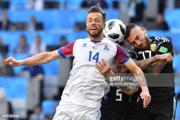 Iceland's defender Kari Arnason heads the ball with Argentina's defender Nicolas Otamendi and Argentina's midfielder Lucas Biglia during the Russia...