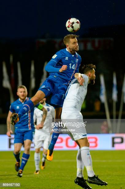 Iceland's defender Kari Arnason wins an aerial battle to head the ball during the FIFA World Cup 2018 qualification football match between Iceland...