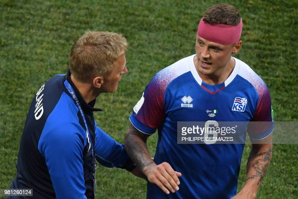 Iceland's defender Ragnar Sigurdsson speaks with Iceland's coach Heimir Hallgrimsson after being substituted following an injury during the Russia...