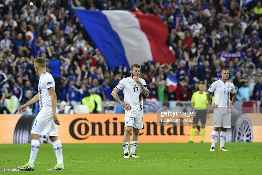Iceland's forward Kolbeinn Sigthorsson (L) midfielder Aron Gunnarsson and Iceland's defender Ragnar Sigurdsson react during the Euro 2016 quarter-final football match between France and Iceland at the Stade de France in Saint-Denis, near Paris, on July 3, 2016. SCHWARZ
