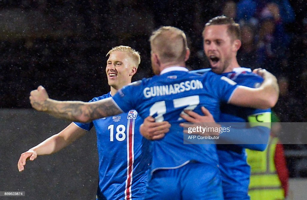 Iceland's Hordur Magnusson, Iceland's midfielder Aron Gunnarsson and Iceland's midfielder Gylfi Sigurdsson celebrate after the FIFA World Cup 2018 qualification football match between Iceland and Kosovo in Reykjavik, Iceland on October 9, 2017. Iceland qualified for the FIFA World Cup 2018 as smallest country ever after beating Kosovo 2-0 at home in Reykjavik. / AFP PHOTO / Haraldur Gudjonsson / ALTERNATIVE