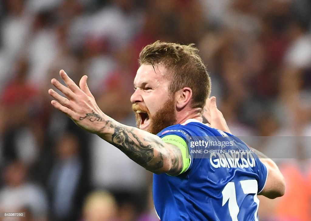 TOPSHOT - Iceland's midfielder Aron Gunnarsson celebrates at the end of the Euro 2016 round of 16 football match between England and Iceland at the Allianz Riviera stadium in Nice on June 27, 2016. /