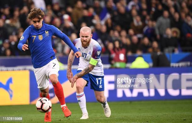 Iceland's midfielder Aron Gunnarsson vies for the ball with France's forward Antoine Griezmann during the UEFA Euro 2020 Group H qualification...