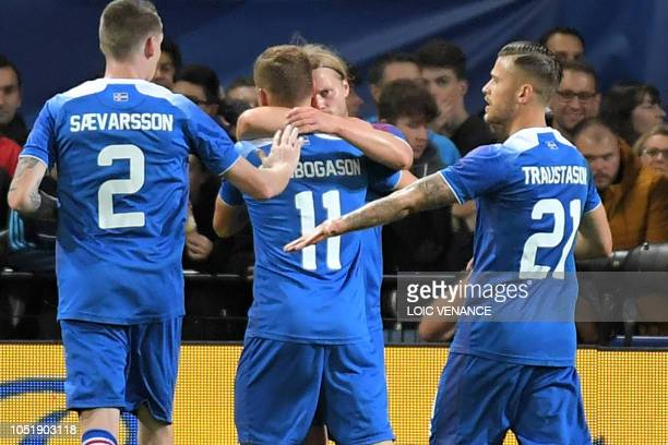 Iceland's midfielder Birkir Bjarnason celebrates with teammates after scoring a goal during the friendly football match between France and Iceland at...