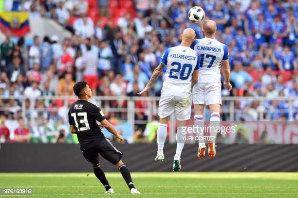 TOPSHOT Iceland's midfielder Emil Hallfredsson and Iceland's midfielder Aron Gunnarsson head the ball next to Argentina's midfielder Maximiliano Meza...