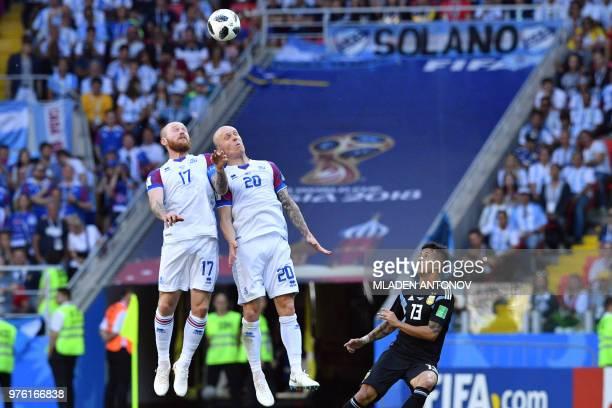 Iceland's midfielder Emil Hallfredsson and Iceland's midfielder Aron Gunnarsson head the ball next to Argentina's midfielder Maximiliano Meza during...