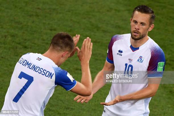 Iceland's midfielder Gylfi Sigurdsson celebrates with Iceland's midfielder Johann Gudmundsson after scoring a goal during the Russia 2018 World Cup...