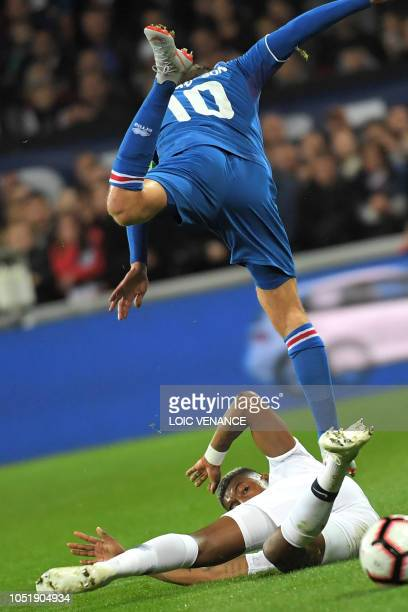 Iceland's midfielder Gylfi Sigurdsson jumps over France's defender Presnel Kimpembe during the friendly football match between France and Iceland at...