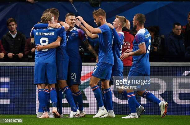 Iceland's midfielder Kari Arnason is congratulated by teammates after scoring a goal during the friendly football match between France and Iceland at...