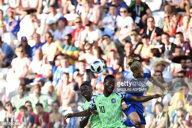 TOPSHOT Iceland's midfielder Rurik Gislason heads the ball with Nigeria's defender Kenneth Omeruo and Nigeria's midfielder John Obi Mikel during the...