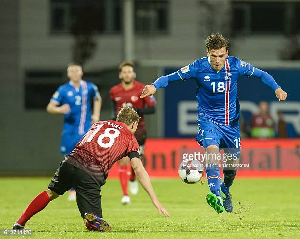 Iceland's midfielder Theodor Bjarnason and Turkey's forward Caner Erkin vie for the ball during the 2018 World Cup qualifier football match of...