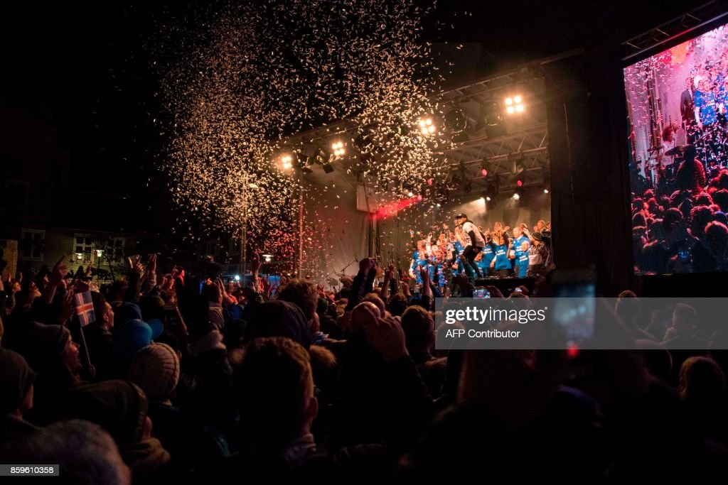 TOPSHOT - Iceland's national team football players and coaching staff celebrate with fans at Ingolfstorg square in the centre of Reykjavik after the FIFA World Cup 2018 qualification football match against Kosovo in Reykjavik, Iceland on October 9, 2017. Iceland qualified for the FIFA World Cup 2018 as smallest country ever after beating Kosovo 2-0 at home in Reykjavik. / AFP PHOTO / Halldor KOLBEINS