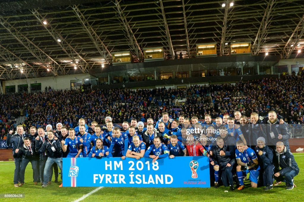 Iceland's players and coaching staff celebrate after the FIFA World Cup 2018 qualification football match between Iceland and Kosovo in Reykjavik, Iceland on October 9, 2017. Iceland qualified for the FIFA World Cup 2018 as smallest country ever after beating Kosovo 2-0 at home in Reykjavik. / AFP PHOTO / Haraldur Gudjonsson / ALTERNATIVE